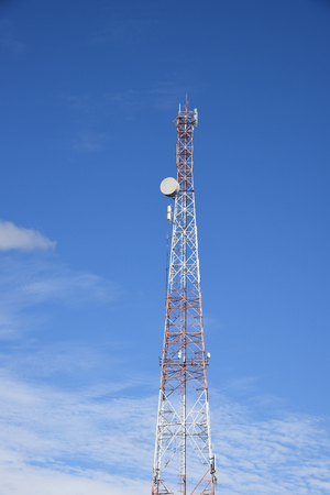 telecommunication tower (transmitter, sender), broadcast, television (TV) and telephone pole, partially red and white paint strips, deep blue sky, view from below on background clear sky