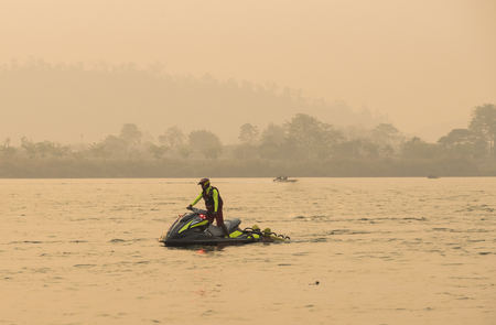 grab: Lifeguard on jetskis with two sporters grab in stern floating in river in triahlon,Thailand. Stock Photo