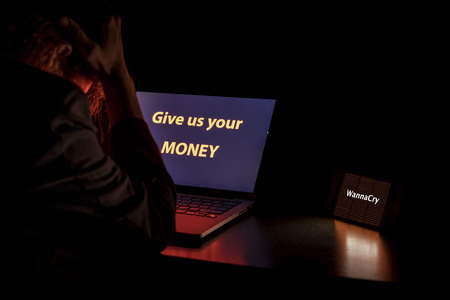 Young Asian man frustrated, confused and headache by WannaCry ransomware attack on desktop screen, notebook and smartphone, cyber attack internet security concept