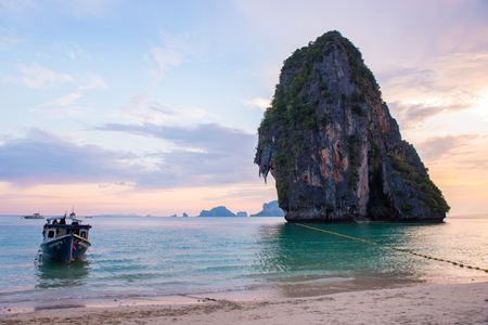 Pinky sky with boat at Railay beach in Krabi Thailand Stock Photo
