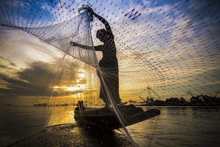背景に日の出と大きな魚網を持つ漁師のシルエット