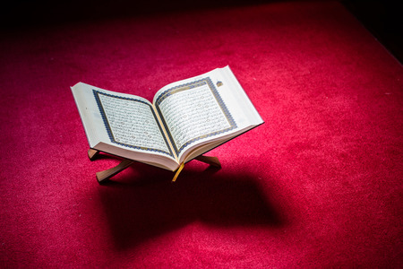 Holy book of Koran on stand on red carpet with vignetting affect.