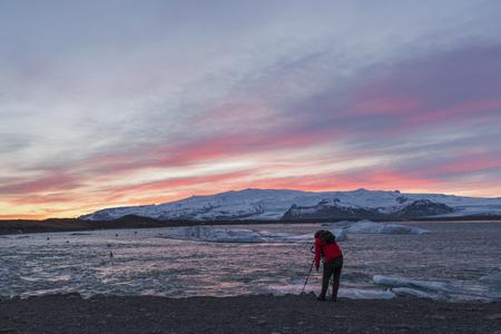photographer man with camera and tripod take photo of beautiful sunset ay jokulsarlon glacier lagoon ,south coast Iceland in winter.