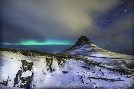 Colorful Aurora Borealis or better known as The Northern Lights and winter milky way over Kirkjufell, Iceland with starry night milkyway. Stock Photo