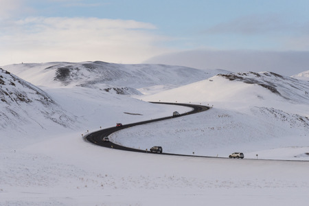 S-curved asphalt road leads to the snow capped mountains in volcanic area in north Iceland ,Iceland winter trip theme.