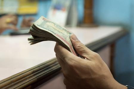 Hand of man hold Nepalese money after changemoney at exchange money shop in Kathmandu Nepal