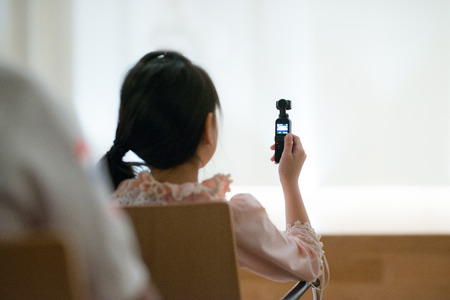 Bangkok,Thailand - March 23, 2019 : Little girl hand hold DJI pocket record clip of indoor concert in musical school. Archivio Fotografico