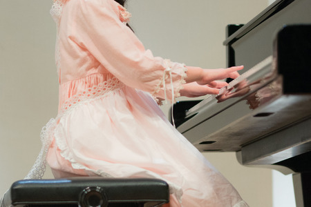 Hand of girl in beautiful dress playing piano,performance in musical school.