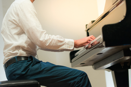 Hand of man playing or practice piano,performance in musical school.