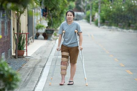 Femme handicapée avec des béquilles ou un bâton de marche ou une genouillère debout avec le corps entier. Banque d'images