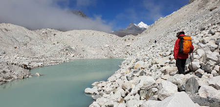 Man with backpack walk on glacier malt on ground near Gokyo lake in Everest base camp route in Nepal.