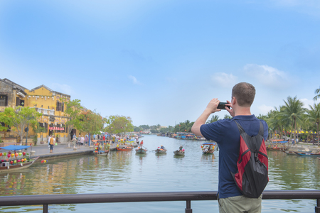 Western tourist man use smart mobile phone take photo of Hoi an river view in old town Vietnam. Banco de Imagens