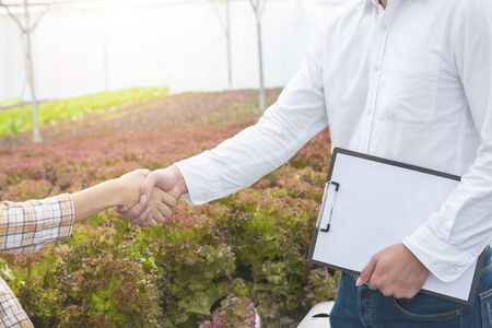 Businessman hand hold contract and asian woman farmer success deal contract in greenhouse hydroponic organic farm, Small business entrepreneur and organic vegetable farm and healthy food concept Standard-Bild