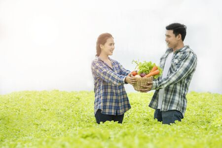 Asian man farmer and asian woman gardener hand hold basket of colourful color vegetable together in organic, cooperation Small business entrepreneur and organic vegetable farm and healthy food concept