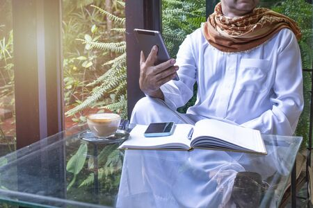 pakistani muslim Man working on tablet computer in coffee shop, hand hold tablet and write book with coffee. business freelance concept. Banque d'images - 129296082