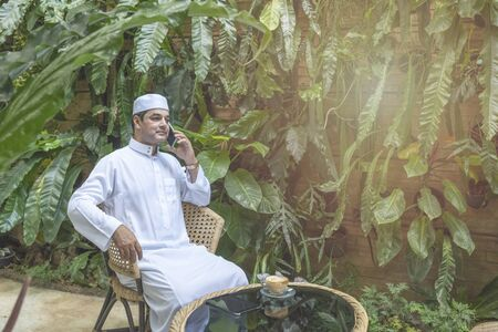 Pakistani business asian man using smart mobile phone, talk with serious face wear muslim dress sit in coffee shop, freelance business concept. Banque d'images - 129296115
