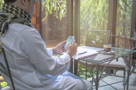 Arab muslim businessman working and using smart mobile phone on table in coffee shop, freelance business concept. Banque d'images - 129296155