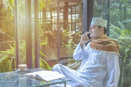 Pakistan business asian man using smart mobile phone, talk with serious face wear muslim dress sit in coffee shop, freelance business concept. Banque d'images - 129296173