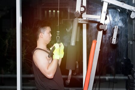 Strong muscular asian man lifting weights exercise his in fitness gymnasium,sport and healthy concept.