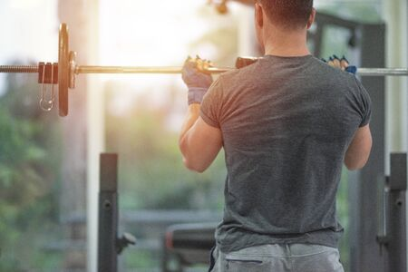 Back side od strong muscular asian man lifting weights exercise his in fitness gymnasium,sport and healthy concept.