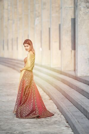 Beautiful portrait asian woman dress in thai silk fashion evening dress act like model and look at camera.