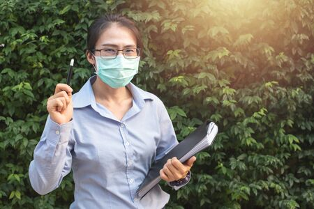 Young asian woman wearing glasses and face mask protect filter pm2.5 anti pollution, anti smog and viruses,left hand hold document file right hand show pen. Air pollution, environmental concept.