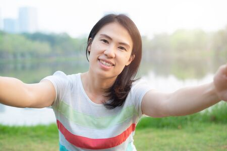 Portrait of asian woman take photo selfie,she smile face and happy,sit in green public park. Stock Photo