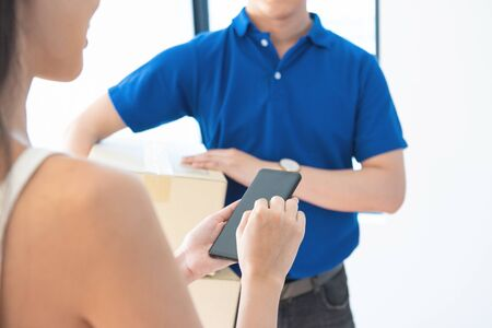 View of young asian woman appending signature in digital smart mobile phone after receiving parcel from courier delivery man at home.AI Technology transportation concept.