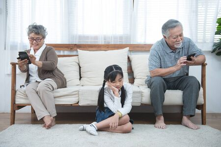In quarrel elderly mother grown up daughter sit on couch separately having conflict, intergenerational misunderstanding, adult grandchild grandma difficult bad relations different generations concept 스톡 콘텐츠