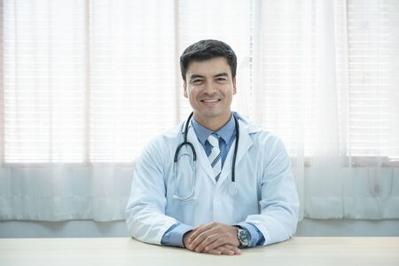 Young doctor caucasian man sitting at the desk at his working place and smiling looking at camera. Perfect medical service in clinic. Happy future of medicine and healthcare. Archivio Fotografico