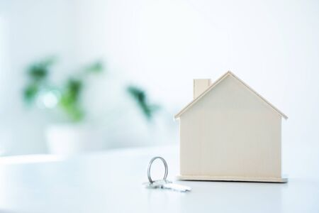 House shape toy with keychain on white table and blank background. Banque d'images