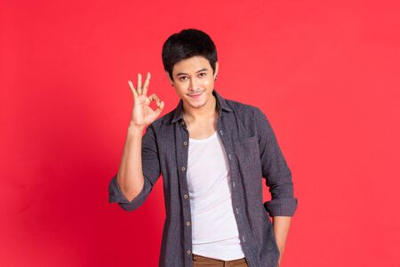 Portrait of happy young asian man dress in casual informal smiling and posing with cheerful and okey hand sign isolated on red background.
