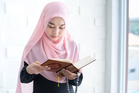 Beautiful asian female Muslim woman in modern kurung and hijab, read quran. Standard-Bild
