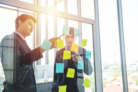 Two person coworker young asian businessman in formal dress communication on posit on wall in modern workplace.