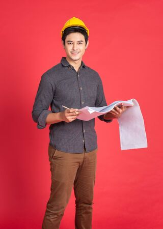 Young handsome asian man in casual dress with yellow hardhat hand holding paperwork blueprint in architect and engineer worker isolated in red background in studio.