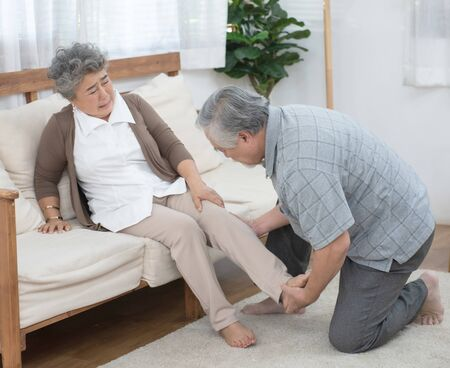 Senior elder asian man help his wife to sit on coach after fall down and get injury on leg or ankle in living at home.
