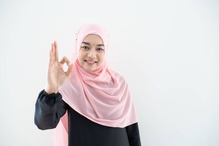 Half length portrait of asian beautiful Muslim young woman wearing business attire and hijab with mixed poses and gestures isolated on grey background. Suitable for technology, business finance theme. 免版税图像