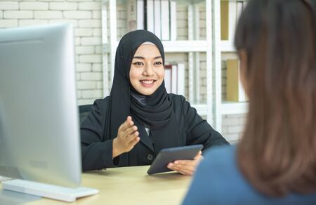 Happy asian muslim businesswoman sales manager shake hand of asian lady client make deal with female customer at meeting with laptop, diverse women partnership, respect and collaboration concept