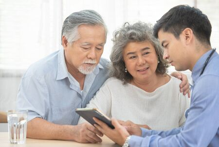 Elder senior old asian couple meeting specialist professional caucasian doctor visit at home consultant two retirement patient after checkup,health care and medical concept.