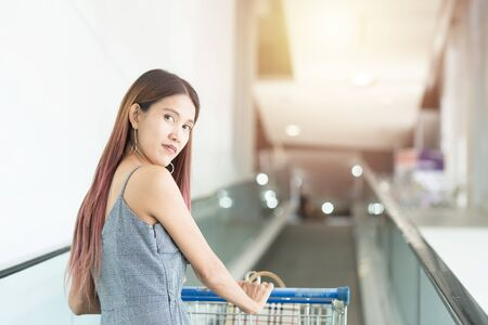 Asian shopper woman with shopping cart on moving walkway up to second floor shopping mall.