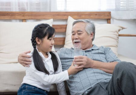 Happy asian senior elderly grandfather have grandchild look after and take care with giving milk and kiss on cheek while sitting on sofa at home,retirement health lifestyle concept.