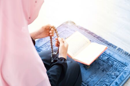 Asian young beautiful muslim woman pray with beads and read quran sit on carpet mat