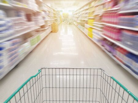 Trolley empty shopping cart on isle with motion blur of product shelf in supermarket, coronavirus covid-19 crisis critical lockdown shopper go stockpiling goods before run out of products. 版權商用圖片