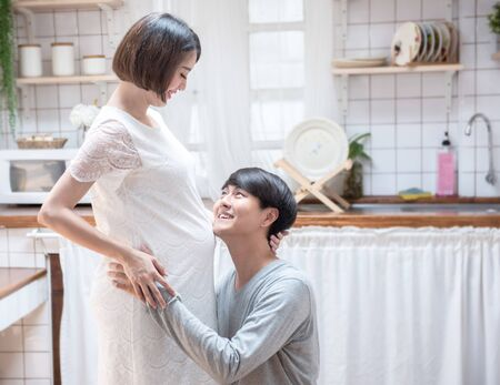 Happy young asian man going to be father sit on knee look at woman with smile. Happy mature man leaning to his pregnant wife belly and smiling, health care and love of pregnancy mother's day concept.