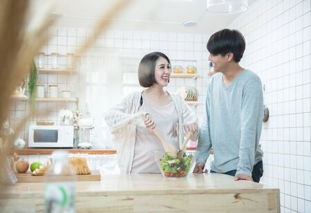 Asian man and pregnancy woman stand in kitchen at home.Father stand and look mother tummy mid salad feeling love expecting about future newborn baby. Love and care of pregnant mother's day concept.