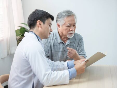 Young caucasian doctor read and explaining consult medical test document for asian elder senior man while visit patient at home.healthcare and medical concept. Banque d'images