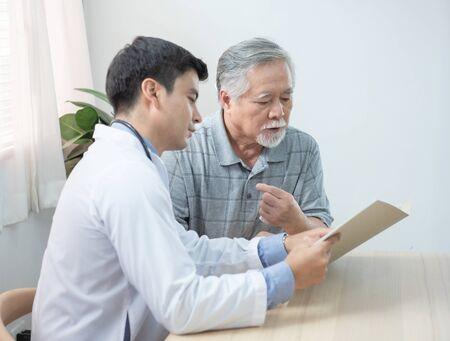Der junge kaukasische Arzt liest und erklärt das medizinische Testdokument für den asiatischen älteren älteren Mann, während er den Patienten zu Hause besucht. Standard-Bild
