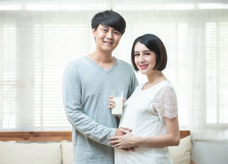Young happy father prepare milk glass for pregnant mother. Asian Daddy takes care and embrace pregnant woman with love,Space for text.