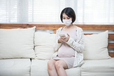 Asian pregnant women wearing medical mask due to illness, dizziness using smart mobile phone with worry, pandemic Wuhan coronavirus (COVID-19) health care concept. 版權商用圖片