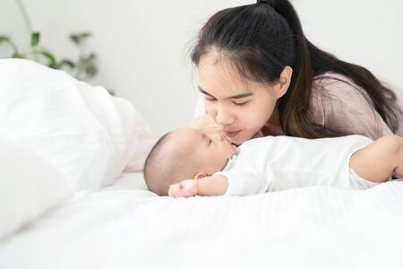 Close up beautiful young asian mother kissing newborn baby on bed. Healthcare and medical. asian girl love lifestyle. Asia mother's day concept banner with copy space for advertise